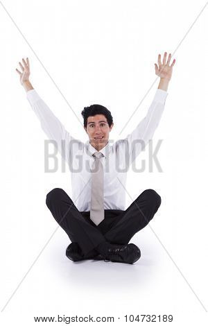 Young and modern businessman sitting on the floor with his arms up (isolated on white)