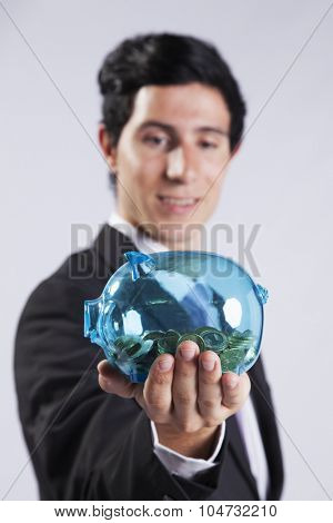 Businessman showing his business profit on a transparent piggy bank full of money (isolated on gray)