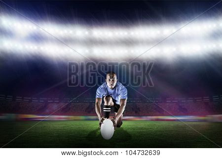 Portrait of rugby player kneeling and holding ball against rugby stadium