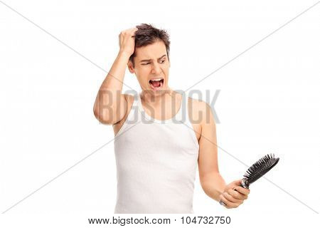 Angry young man loosing hair and holding a hairbrush isolated on white background