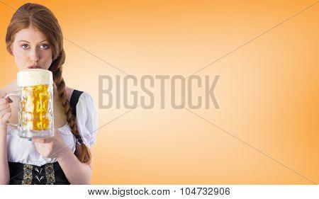 Oktoberfest girl drinking jug of beer against orange vignette