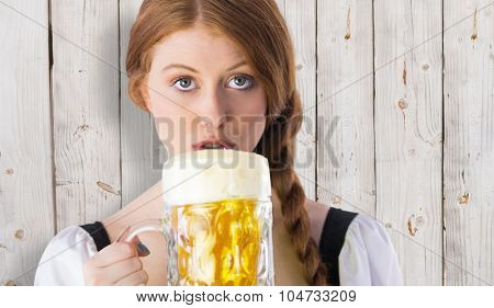 Oktoberfest girl drinking jug of beer against wooden background