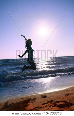 woman jump on the beach at sunset, silhouette, full body shot, side view