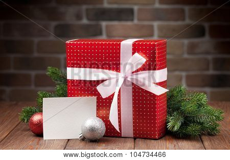 Christmas gift box, greeting card and fir tree branch on wooden table
