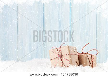 Christmas gift boxes in snow and wooden background with copy space
