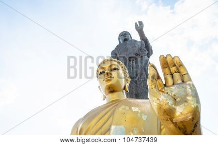 Golden Buddha Statue Focused On Head In Peace Hand Sign (okay Pose)  With Big Granite Buddha Statue