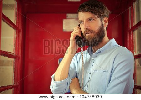 Man doing a call in a telephone box