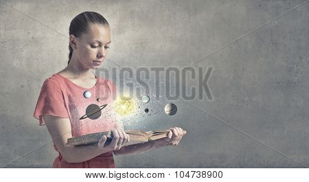 Young woman with book exploring planets of sun system