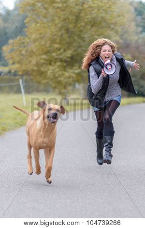 Woman Running With Her Dog And A Megaphone