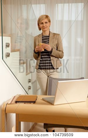 Young blonde woman standing behind desk, drinking tea, daydreaming.