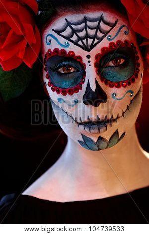 Closeup portrait of scary woman in santa muerte halloween makeup.