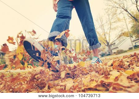 Child walking and kicking fall leaves. Focus on leaves in center.  Motion blur on legs, Instagram filtered effect.