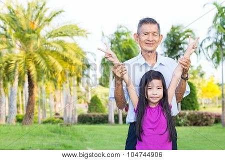 Grandfather And Grandchild Have Fun And Play In Park