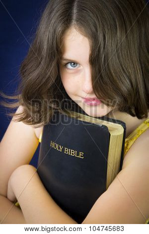 Portrait Of Beautiful Little Girl Holding Holy Bible