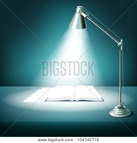 Opened book on table with desk lamp