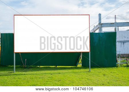 Blank bill board on green field at construction site