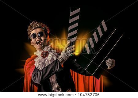 Portrait of a extravagant vampire with a clapper board. Halloween. Cinema industry.