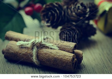 Cinnamon Sticks Bundle, Holly And Fir Cones On Oak Table - Retro Hues