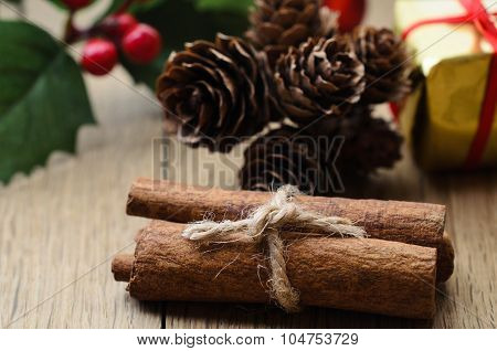 Cinnamon Sticks Bundle, Holly And Fir Cones On Oak Planked Table