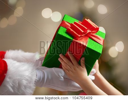 Santa Claus is giving a Christmas gift to child.