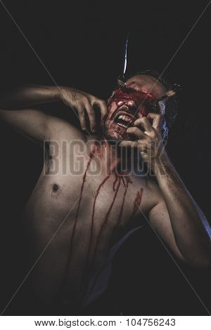 Horror, naked man with blindfold soaked in blood