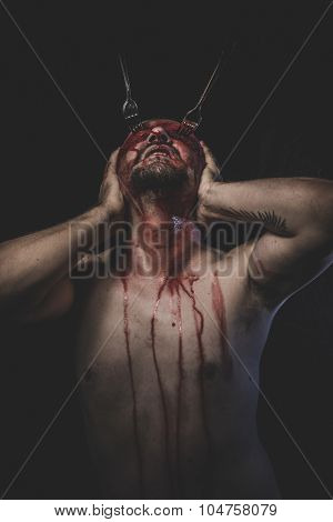 Goth, naked man with blindfold soaked in blood