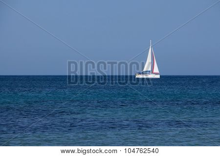White Yacht Traveling With Sails Down On Blue Sea And Sky Horizon