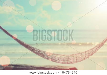 Blurred Hammock On Tropical Beach With Bokeh Sun Light Abstract Background.