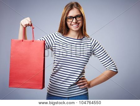 Pretty shopper showing red paperbag and looking at camera