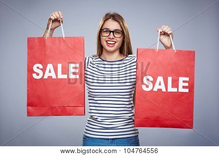 Happy consumer with two red shopping bags