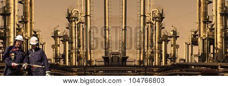giant refinery with two oil and gas workers at sunset , panoramic view
