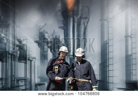 oil and gas workers with refinery in background, slight zoom effect