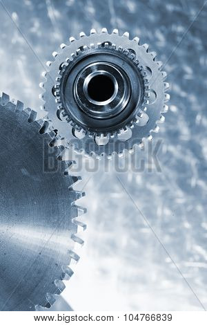 small gear around a giant cogwheel, aerospace titanium parts