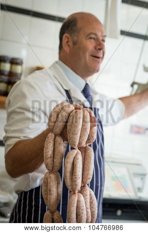 Smiling Butcher Holding Up A String Of Sausages