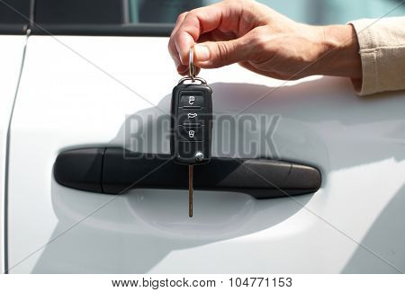 Hand of driver with a car key. Auto rent and sell.