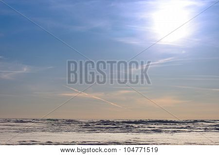 Snow desert and blue winter sky. Mountains on the horizon