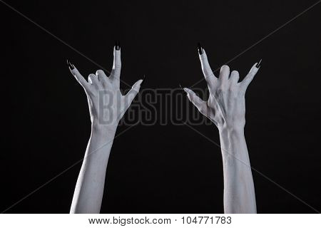 Pale ghost hands showing heavy metal sign, Halloween or music theme