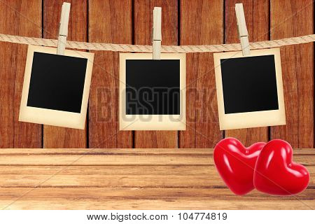 Old Photo Cards Hanging On Rope On Clothespins And Two Red Hearts Over Wooden Background