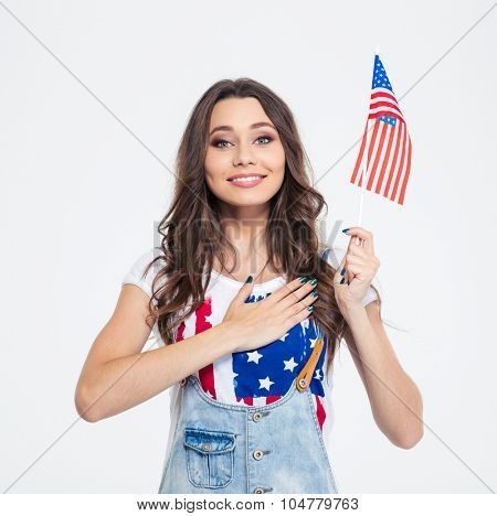 Portrait of a smiling patriotic woman holding USA flag isolated on a white background