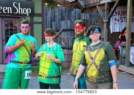 MUSKOGEE, OK - Sept. 12: A group of runners dressed as Ninja Turtles overcome obstacles during the Castle Zombie Run at the Castle of Muskogee in Muskogee, OK on September 12, 2015.