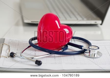 Read Heart And Stetoscope Laying On Cardiogram Chart At Doctor's Working Table