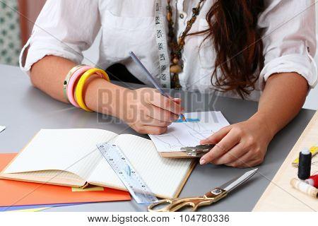 Close-up Of Adult Female Dressmaker Drowing Some Clothing Design