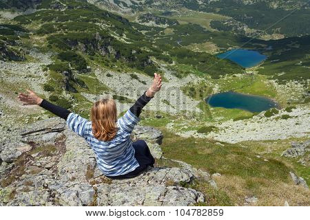 Woman With Raised Hands In Mountain Scenery