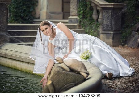Happy bride with bouquet of flower near fountain
