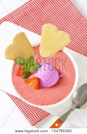 bowl of strawberry soup with scoop of blueberry ice cream and crispy wafers on white cutting board and checkered place mat