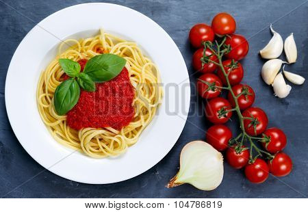 Spaghetti With Marinara Sauce And Basil Leaves On Top, Decorated With Cherry Tomatoes, Garlic, Onion
