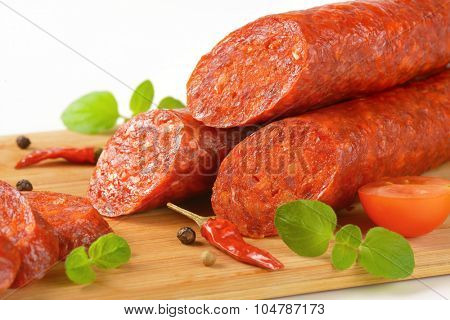 detail of sliced pepperoni sausages on wooden cutting board
