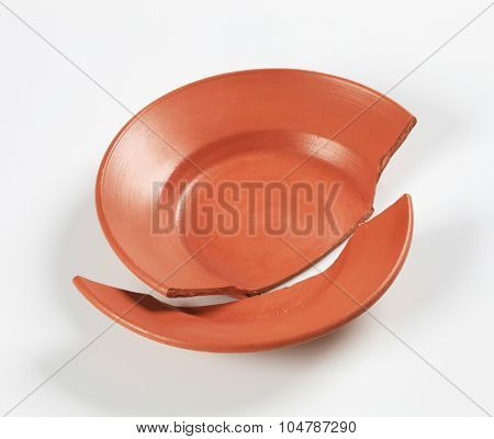 two pieces of a broken terracotta plate