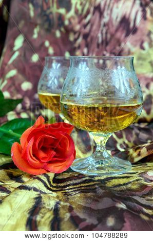 Two Glasses Of Cognac With A Red Rose On A Colored Background