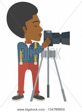 An african-american photographer standing with camera on a tripod vector flat design illustration isolated on white background. Vertical layout.